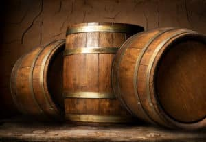 Old wooden barrels in cellar with clay wall